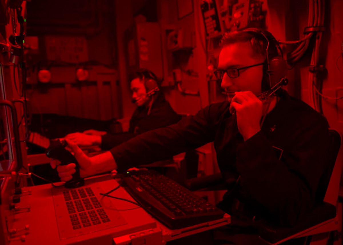 Two sailors sit in a red control room on a ship.