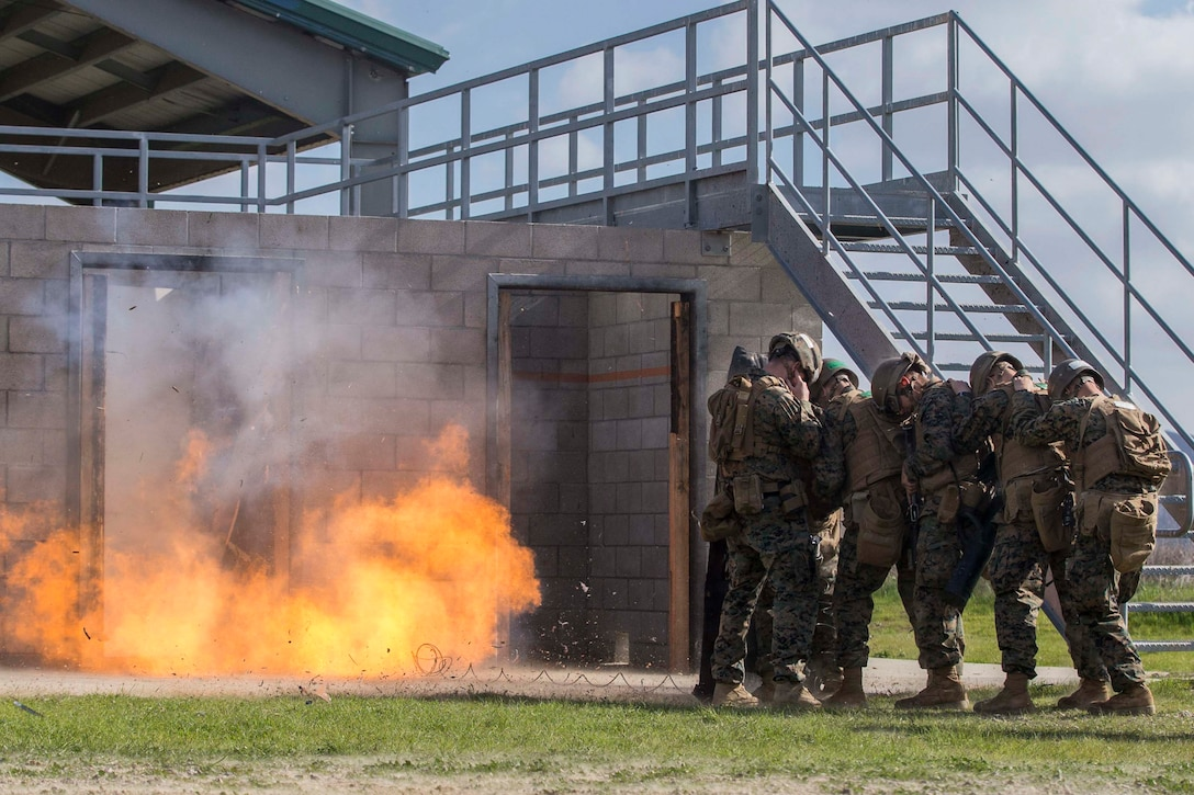 Marines stand huddled together as an explosive device detonates.