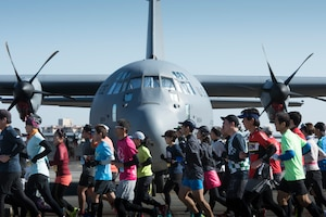 Runners are running in front of an aircraft