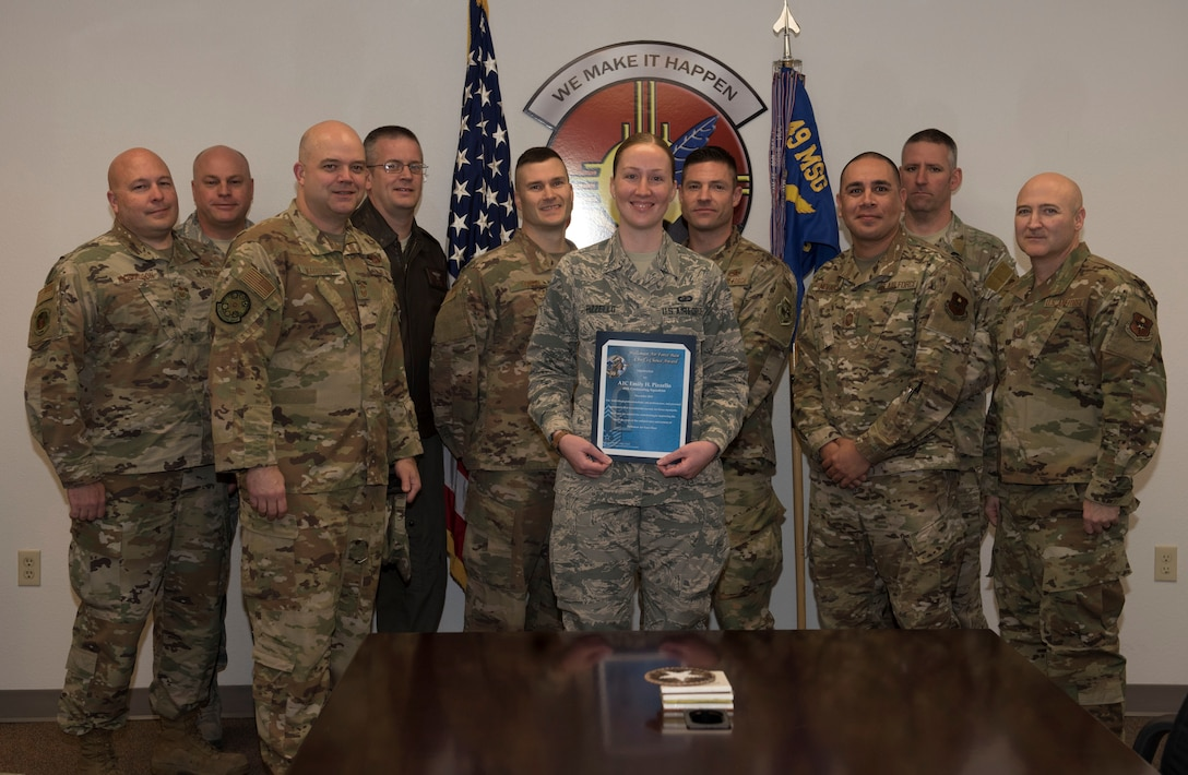 Airman 1st Class Emily H. Pizzello, 49th Contracting Squadron contract administrator and representatives from the Holloman Air Force Base's Chiefs Group pose with during a group photo Jan 21, 2019, on Holloman Air Force Base, N.M. Holloman's Chiefs Group has a monthly recognition program titled Chief's Choice Award, and every month a chief has the honor of choosing a deserving Airman for an outstanding act or for continuous outstanding performance. (U.S. Air Force photo by Staff Sgt. Christine Groening)