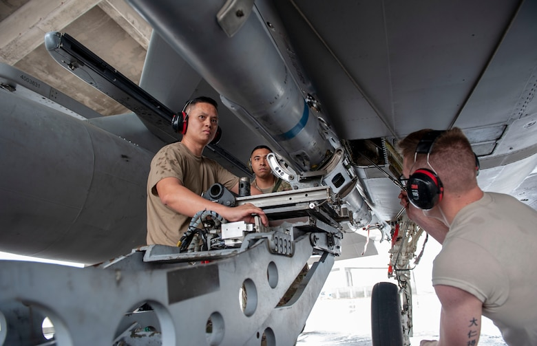 U.S. Air Force Staff Sgt. Chinh Nguyen (left), 67th Aircraft Maintenance Unit load crew chief, and Airman 1st Class Daniel Wolf (right), 67th AMU load crew member, secure an AIM-120 advanced medium-range air-to-air missile onto an F-15C Eagle aircraft during the annual weapons load competition at Kadena Air Base, Japan, Jan. 17, 2020. Each team must load the munition onto an F-15C Eagle aircraft with speed and precision. (U.S. Air Force photo by Naoto Anazawa)