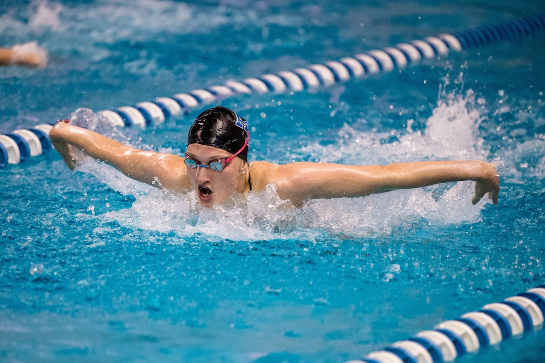 An  Air Force cadet swims the butterfly stroke in a pool.