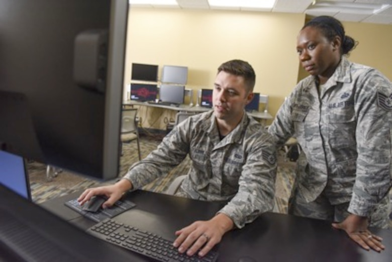 Staff Sgt, Jacob Gann provides an intelligence report to Tech. Sgt. Ashlee Harper-Johnson.