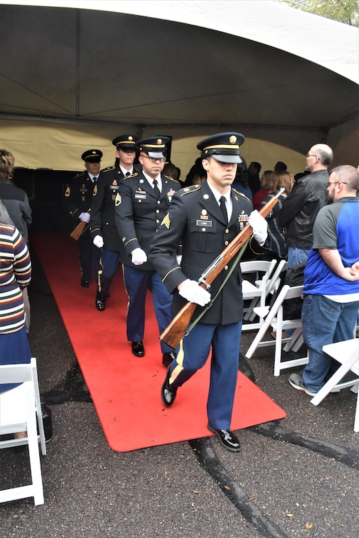 Soldiers in dress blue uniform with service cap and white gloves march down a red carpet in the middle of a crowd two hold rifles.