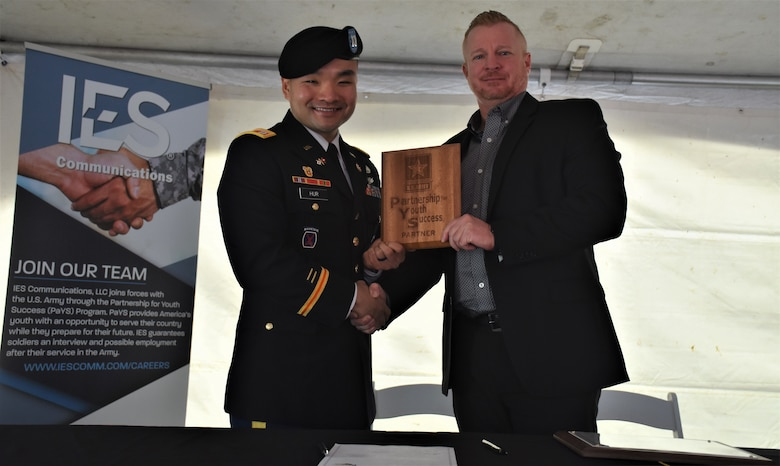 Male Soldier in blue dress uniform and beret shakes hands with male in suit while holding a wood plaque. An IES banner is standing to the left of the duo.