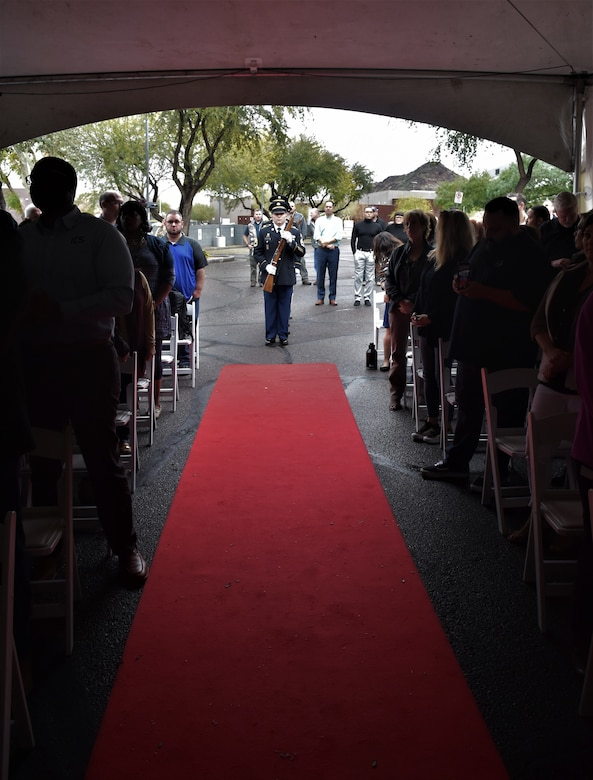 People standing in chairs on both sides of a red carpet with male Soldiers in blue dress uniform with ceremony rifles standing at the end of the carpet.