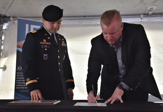 Male Soldier in blue dress uniform with beret stands next to and watches civilian man in dark suit signing a piece of paper with a pen.