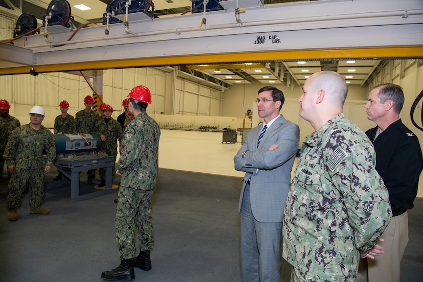 Defense Secretary Dr. Mark T. Esper stands with service members in a large building.