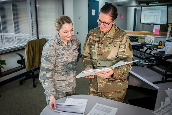 Air Force members look over documents in the Force Support Squadron office.