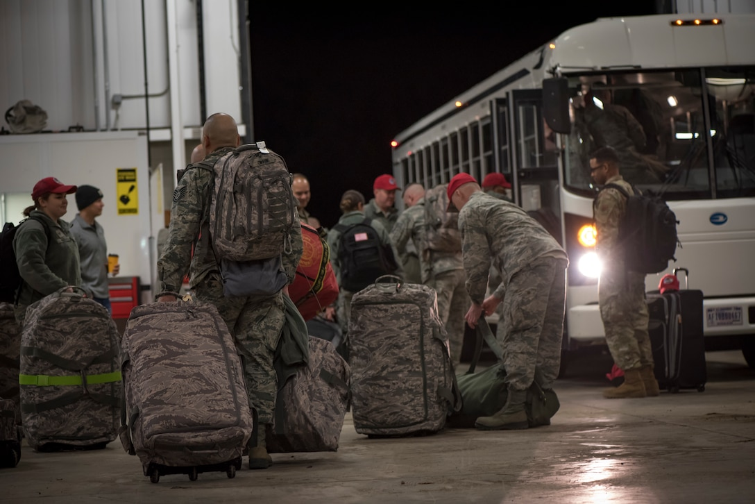 Photo of 200th RED HORSE members packing up and loading onto a bus.