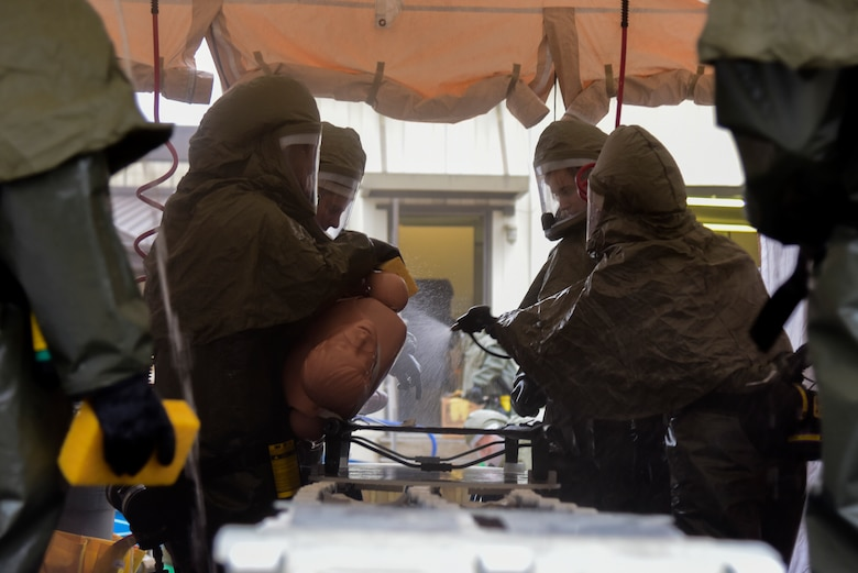 47th Medical Group medics wearing powered, air-purified respirator suits tend to a simulated patient in the in-place patient decontamination tent on Jan. 17, 2020 at Laughlin Air Force Base, Texas. In the event of a chemical, biological, radiological or nuclear disaster, patients who come to the clinic for care would have to go through this cleansing process before being admitted to the clinic. (U.S. Air Force photo by Senior Airman Anne McCready)