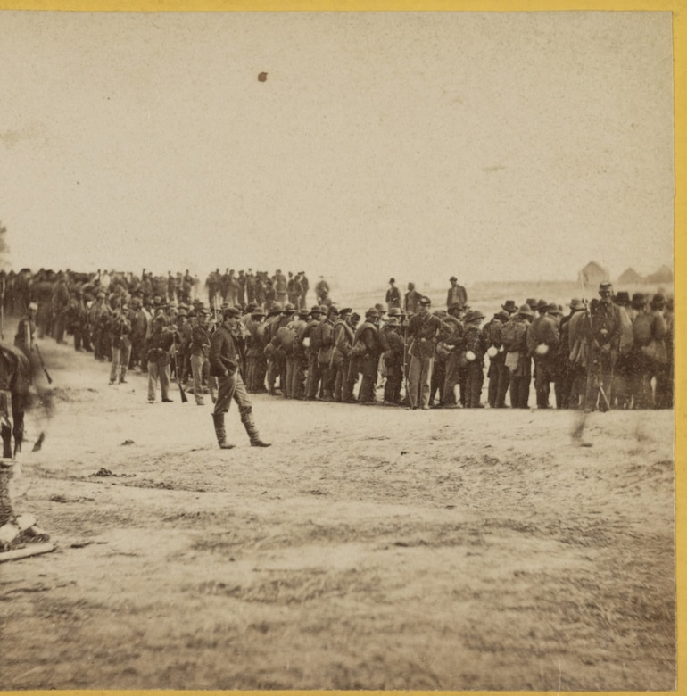 Civil War soldiers stand in a line on a barren field.