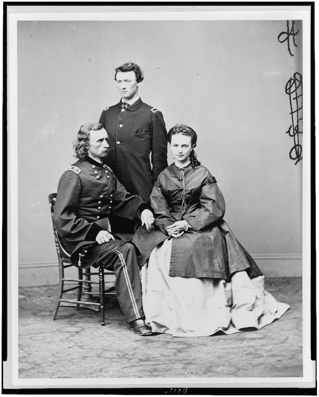 A Civil War Army general sits next to a woman in a long dress. Between them stands another man.