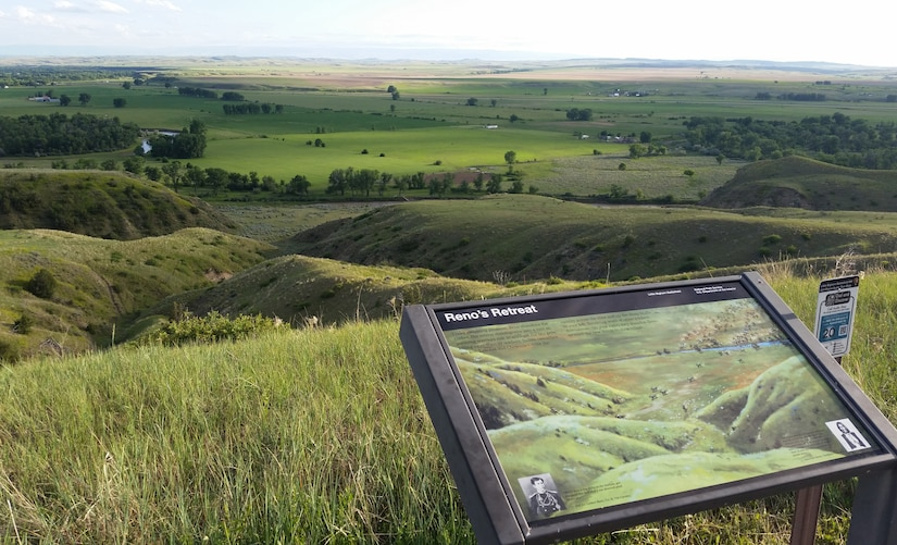 "A plaque labeled ""Reno's Retreat"" marks a spot at the Little Bighorn National Battlefield. In the background is a field of rolling green hills."