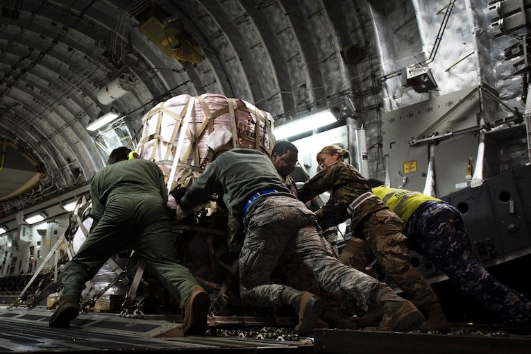 A group of service members push a heavy pallet of supplies up an aircraft ramp.