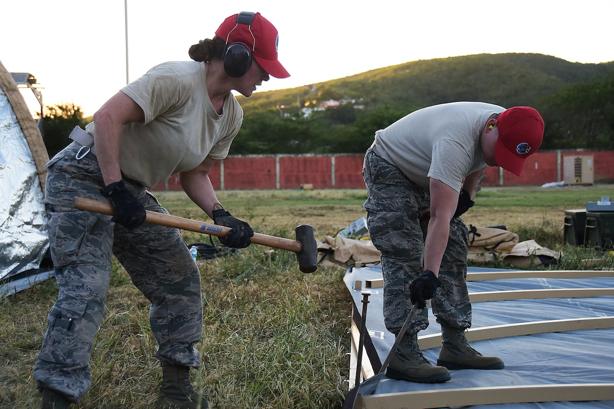 Two service members hammer stakes into the ground as they set up tents.