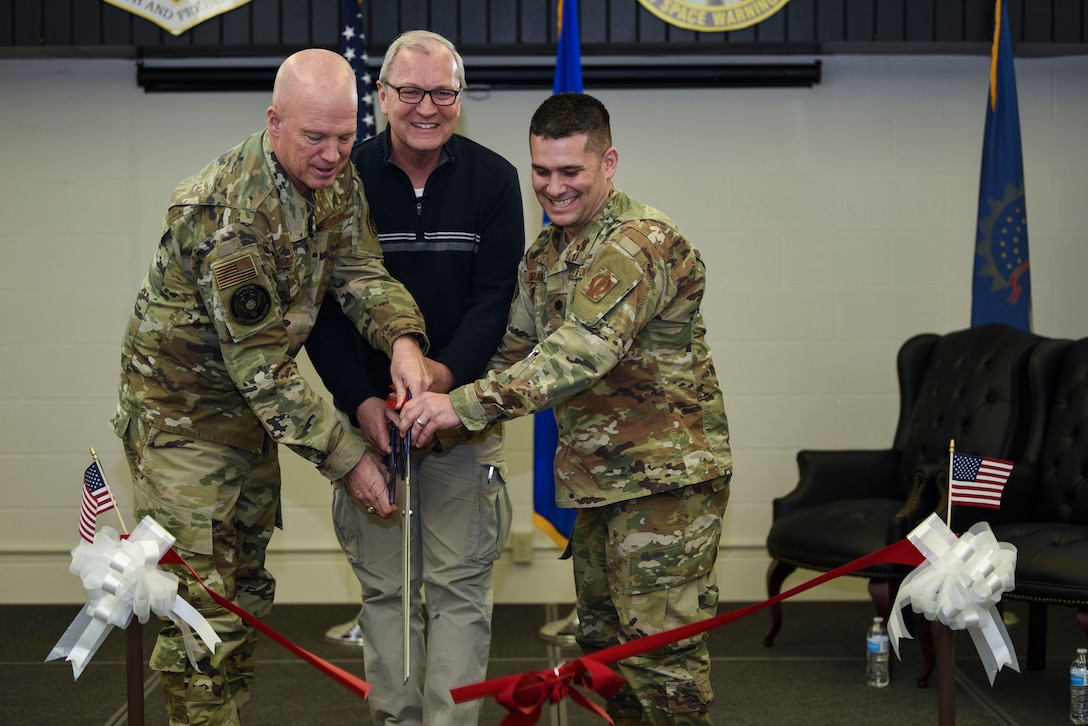 General John Raymond, U.S. Space Force chief of space operations (left), the Honorable Kevin Cramer, U.S. North Dakota senator (middle), and Lieutenant Colonel Ryan Durand, 10th Space Warning Squadron commander (right), cut a ribbon during a ceremony for the opening of the improved 10th SWS Sensitive Compartmented Information Facility Jan. 10, 2020, on Cavalier Air Force Station, North Dakota. The SCIF allows crewmembers to access timely intelligence on space and missile threat systems and adversary capabilities. (U.S. Air Force photo by Senior Airman Melody Howley)