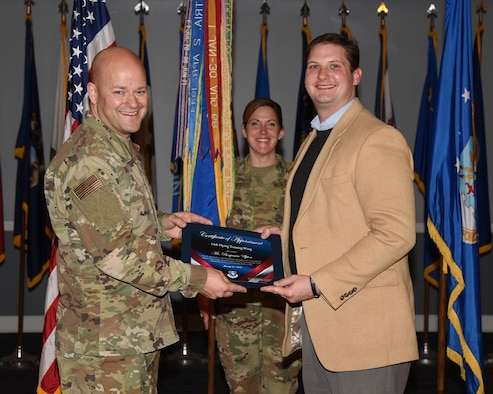 Col. Samantha Weeks (center), 14th Flying Training Wing commander, smiles as Chief Master Sgt. Trevor James (left), 14th FTW command chief, gives a certificate to an honorary commander inductee on Jan. 21, 2020, at Columbus Air Force Base, Miss. As honorary commanders, local leaders will be fully immersed in the Air Force culture and experience the wing's mission of cultivating, creating pilots and connecting first hand. (U.S. Air Force photo by Elizabeth Owens)