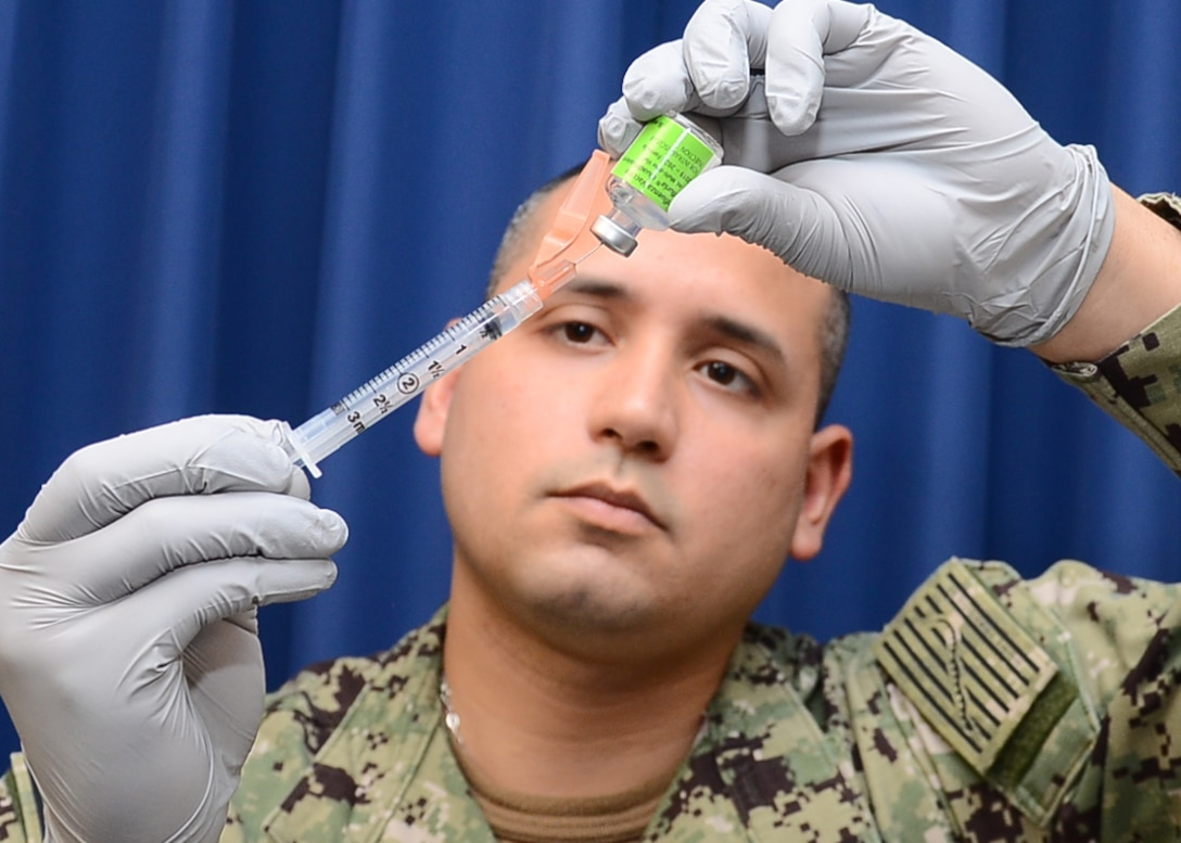 Navy Retail Services Specialist 2nd Class Tomas Vasquez prepares a syringe with the influenza vaccine before administering annual Flu Shots at Naval Health Clinic Corpus Christi.