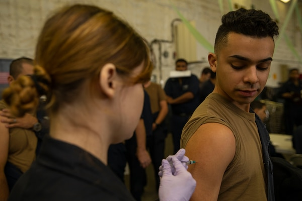 Navy Hospital Corpsman 3rd Class Kindal Kidd, assigned to USS Gerald R. Ford's medical department, administers a flu shot to a sailor in the ship's hangar bay.
