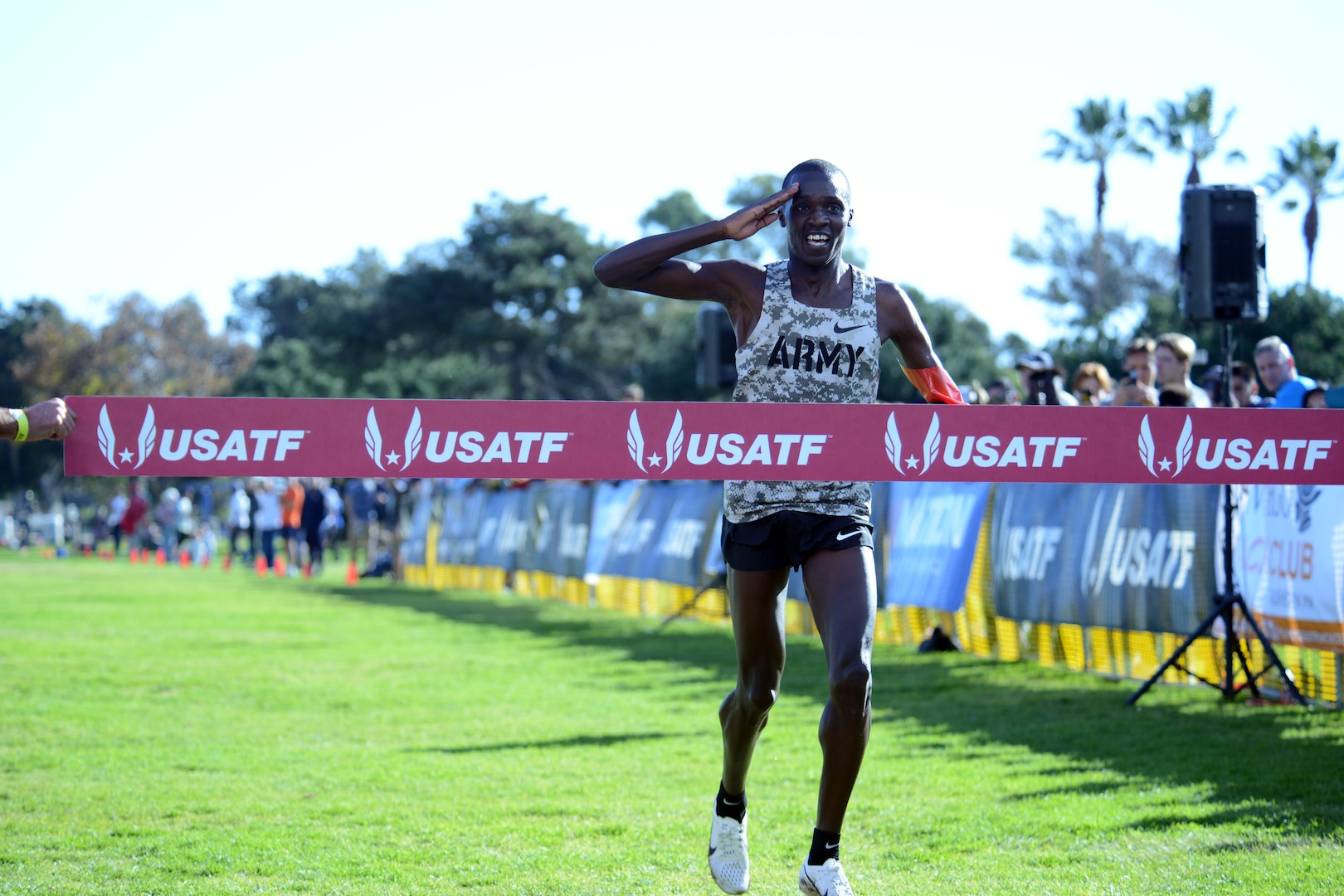Army Cpl. Anthony Rotich salutes just before crossing the finish line to win the Armed Forces Cross Country Championship, run in conjunction with the USA Track and Field senior men 10K race at Mission Bay Park, San Diego, Calif., Jan. 18, 2020. Rotich took gold for both with a time of 30:36.