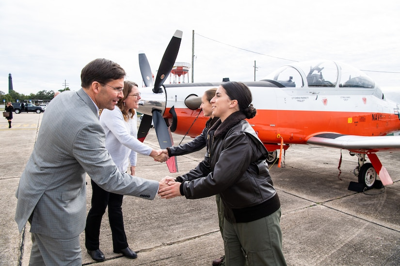 A man in a suit shakes hands with a woman in a military uniform. A military aircraft is in the background.