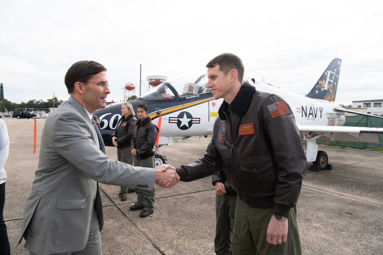 A man in a suit shakes hands with a man in a military uniform.  In the rear, a military aircraft.
