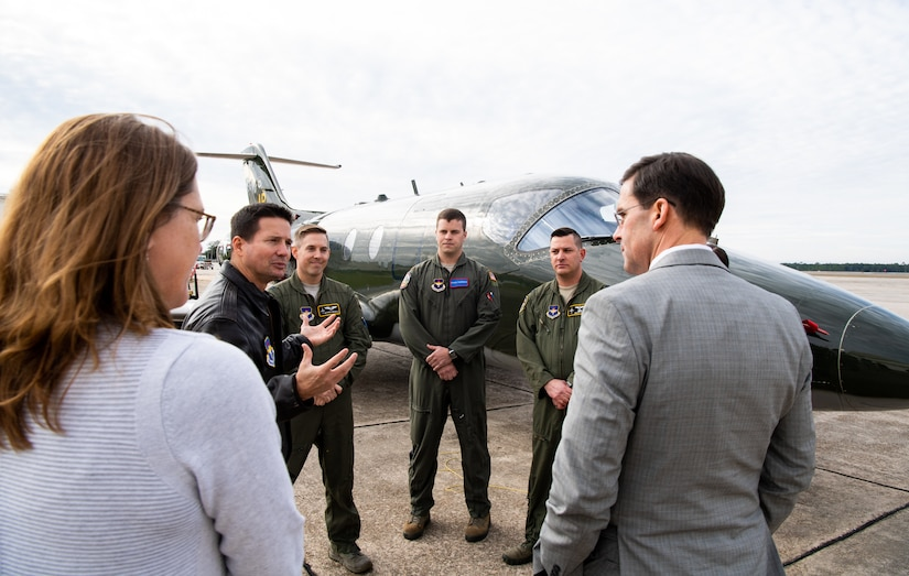A group of people, some in military uniforms, stand in a circle and speak. A military aircraft.is in the background.