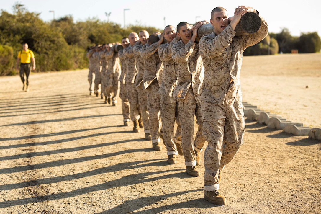 Marine Corps recruits carry a log over their heads.