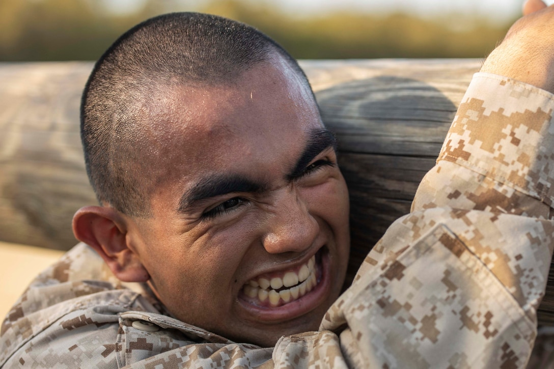 A Marine Corps recruit carries a log over his shoulder.
