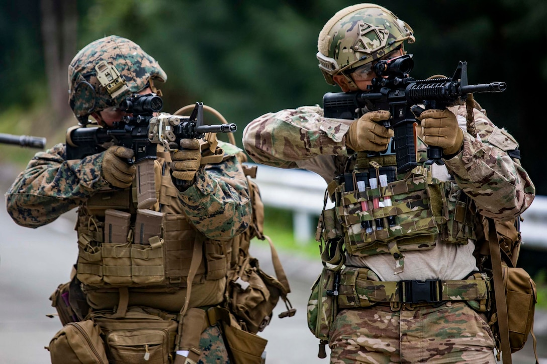 A Marine and an airman stand side by side holding up their weapons.