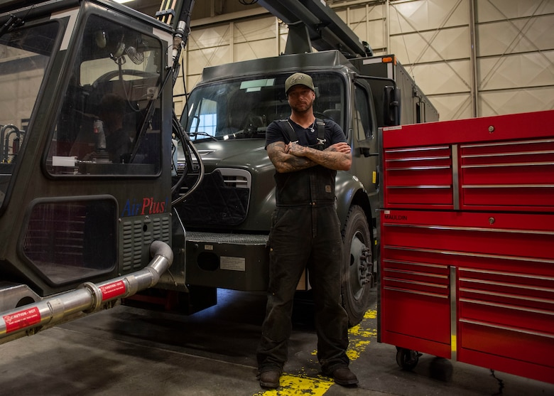 Jessie Mauldin, 673d Logistics Readiness Squadron heavy mobile equipment mechanic, poses for a photo next to a newly modified deicing truck at Joint Base Elmendorf-Richardson, Alaska, Jan. 22, 2019. The modification involves strategically attaching four eyelets to the top of each truck so mechanics can attach a mobile safety harness. Mauldin has taken steps to push his innovation to all heavy mobile equipment maintenance shops Air Force-wide.