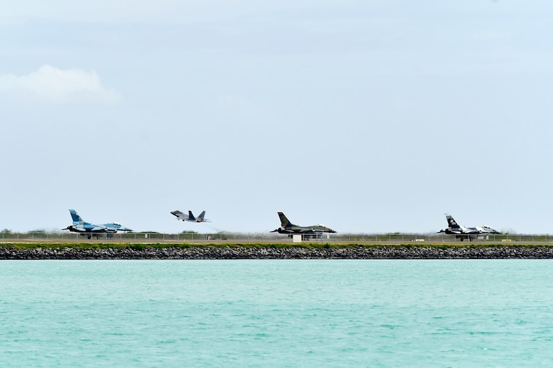 Three F-16 Fighting Falcons assigned to the 18th Aggressor Squadron taxi down the runway while an F-22 Raptor assigned to the Hawaii Air National Guard takes off during Sentry Aloha 20-1 at Joint Base Pearl Harbor-Hickam, Hawaii, Jan. 15, 2020. The 18th AGRS uses mobile training teams to increase U.S. Air Force, Air National Guard and joint partner nations' lethality and readiness. (U.S. Air Force photo by Senior Airman Beaux Hebert)