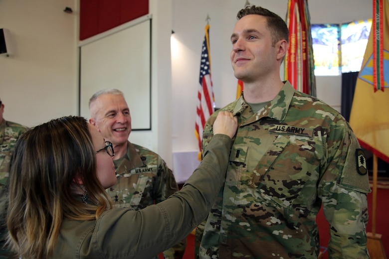 Newly appointed U.S. Army Reserve Chaplain (1st Lt.) Gabriel Pech, 7th Mission Support Command, receives the Army Chaplain cross from his wife, Hannah, while the U.S. Army Chief of Chaplains, Chaplain (Maj. Gen.) Thomas L. Solhjem looks on, during a pinning ceremony held at the Daenner Kaserne Chapel in Kaiserslautern, Germany on January 22, 2020. Pech was the first U.S. Army Reserve officer to complete the Chaplain Candidate Program in Europe.