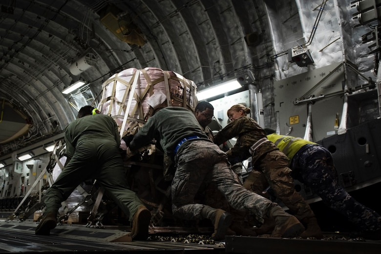 U.S. and Australian airmen worked together to loaded the aircraft with materials to aid in Australian wildfire relief
