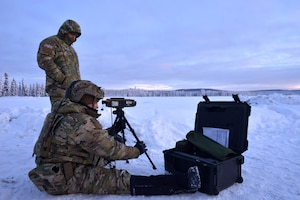 Staff Sgt. evaluates Airman 1st Class as he sets up a ground-portable laser target designator