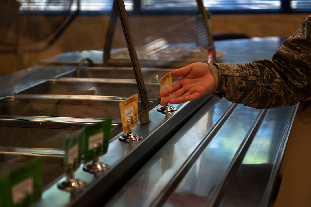 A photo of an Airman pointing to signs on the food line at the dining facility