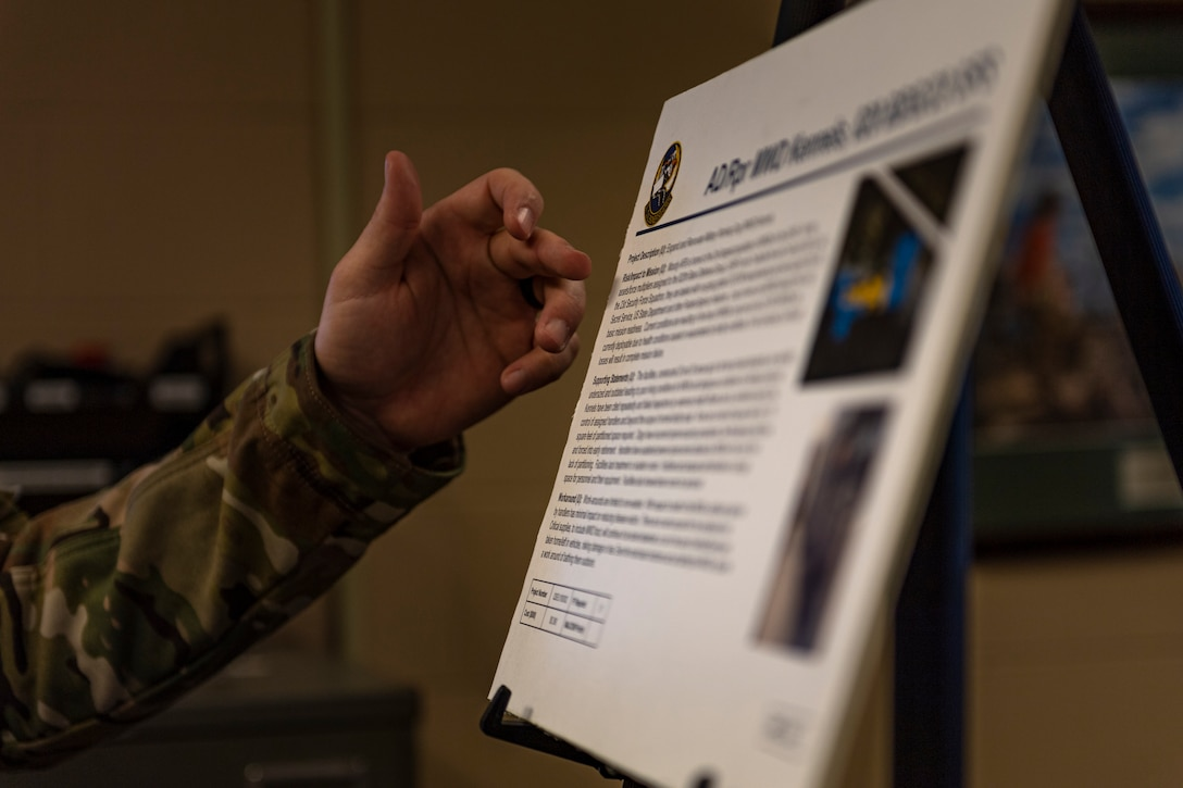 A photo of an Airman pointing to a poster