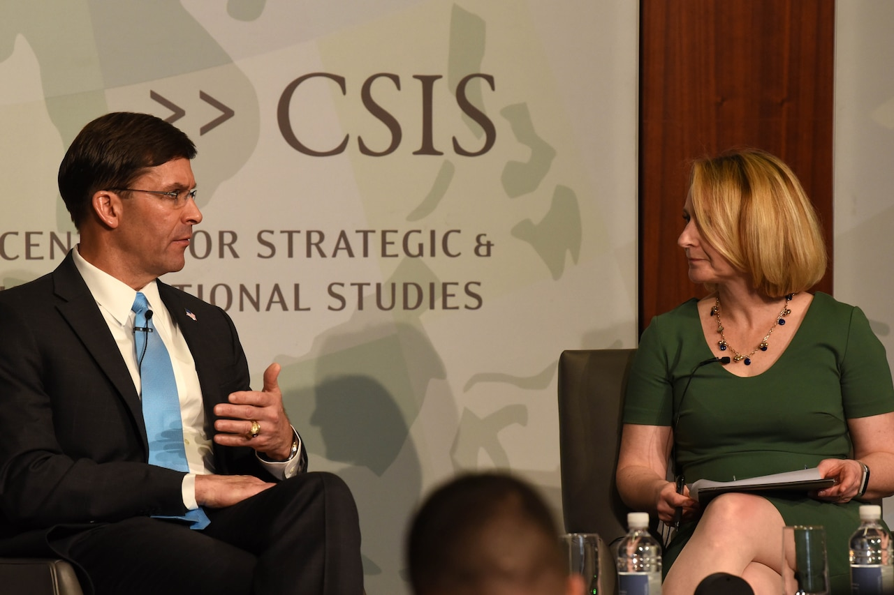Defense Secretary Dr. Mark T. Esper speaks and a woman engage in a discussion before a group of people.