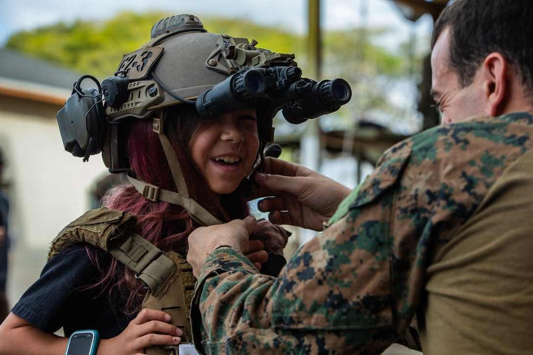 A Force Reconnaissance Marine buckles his helmet on a child during a community interaction, tactical demonstration event in Kapolei, HI, Jan. 19.
