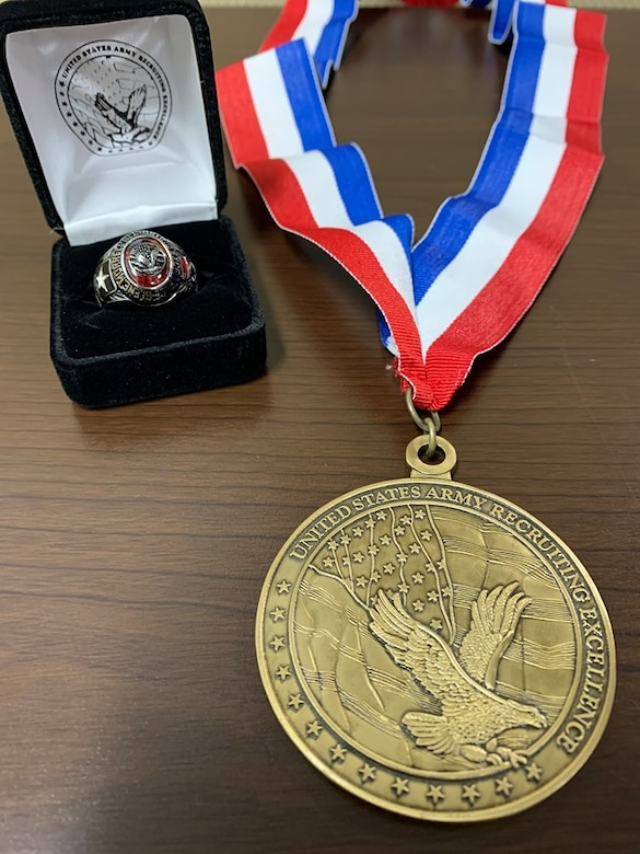 Black and white box with ring inside sitting next to a gold medal on a red white and blue ribbon sitting on a brown table.
