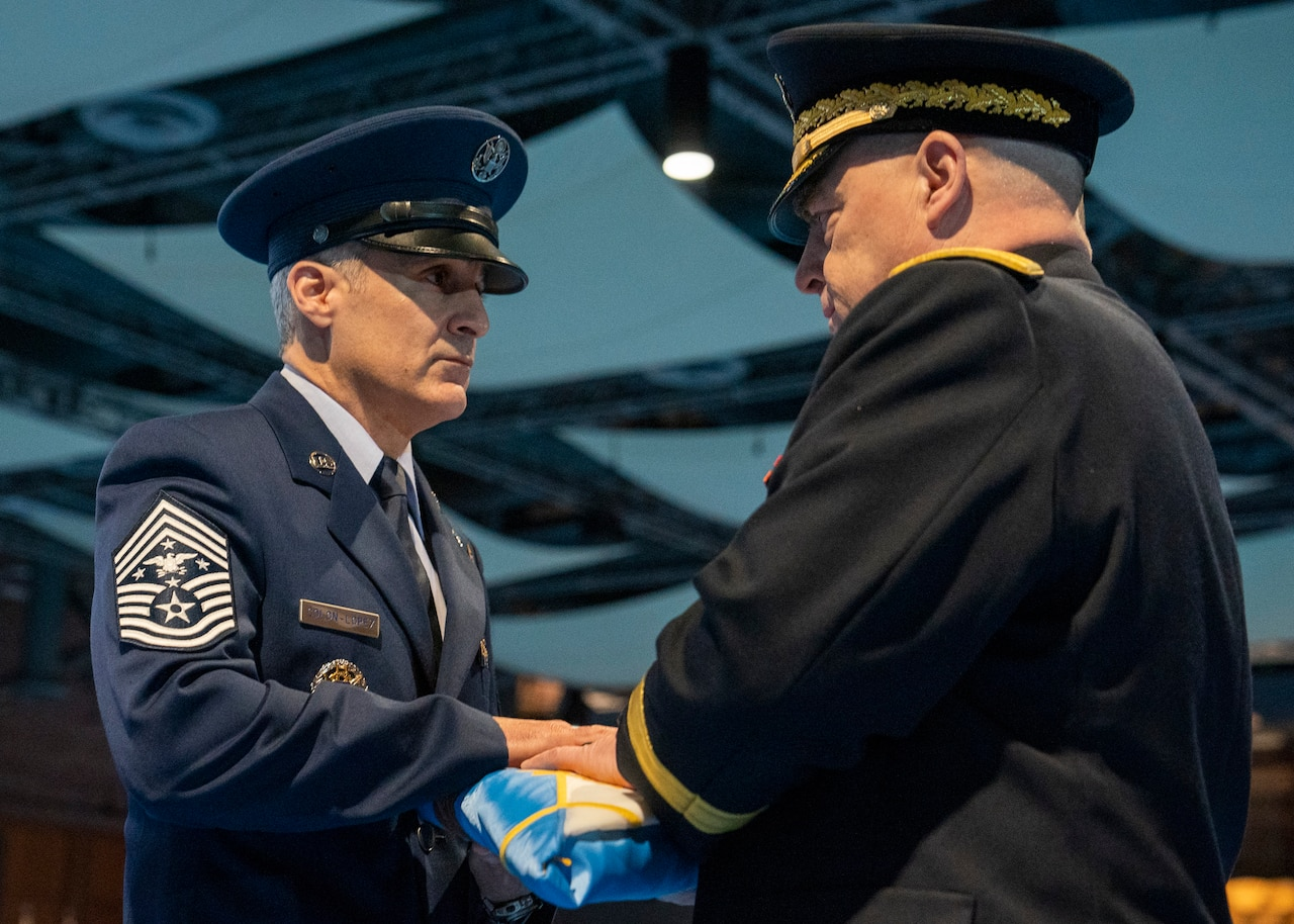 Soldier presents flag to airman.