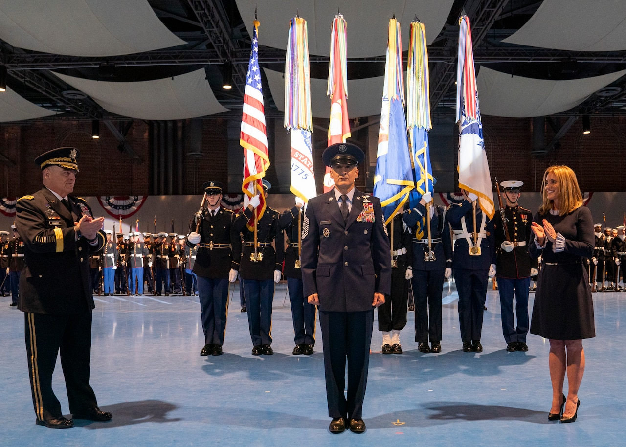 Man stands in front of national, service flags.