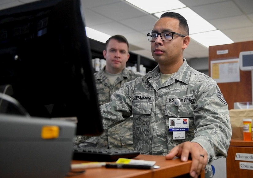 Staff Sgt. Pablo Santamaria, right, a pharmacy technician assigned to the 628th Medical Support Squadron, and Tech. Sgt. Albert Lepine, left, 628th Medical Support Squadron NCO in charge of pharmacy services, learn the ScriptCenter program to load prescriptions into the ScriptCenter machine in the 628th Medical Group Pharmacy, January 21, 2020, at Joint Base Charleston.