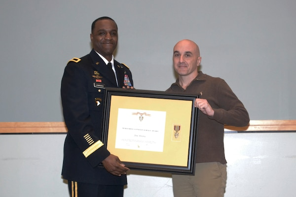Jose Periera, DLA Troop Support Industrial Hardware Technical Quality division chief, receives the Civilian Meritorious Service award from DLA Troop Support Cmmander Army Brig. Gen. Gavin Lawrence Jan. 21, 2020 at DLA Troop Support in Philadelphia.   Periera was one of three IH employees who received the award for their work managing and assisting with the acquisition of roughly 940,000 items for more than 11,000 customers.