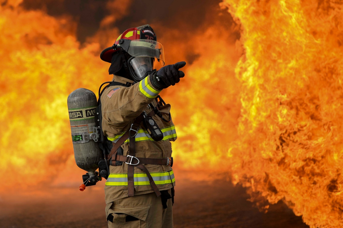 An airman points while wearing a protective suit as fire surrounds.