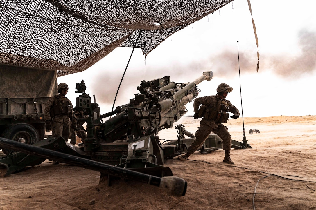 Marines fire a large military weapon.