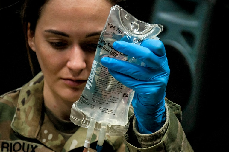 A soldier looks at a medical saline bag in her hand.