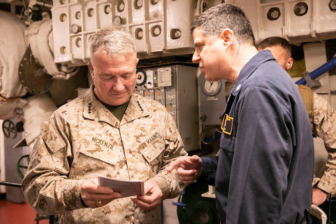 A U.S. Navy officer attached to USS Bataan (LHD 5), right, speaks to U.S. Marine Corps Gen. Kenneth F. McKenzie Jr., the commander of U.S. Central Command, Jan. 23, 2020. McKenzie visited the USS Bataan to discuss security and stability in the region with forward deployed service members. (U.S. Marine Corps photo by Sgt. Roderick Jacquote)
