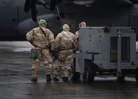 Three Airmen stand near a large grey aircraft in MOPP gear.